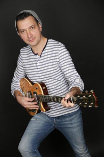 ArtSomer-Gitarrespielend-gestreiftesHemd-gebeugtesKnie